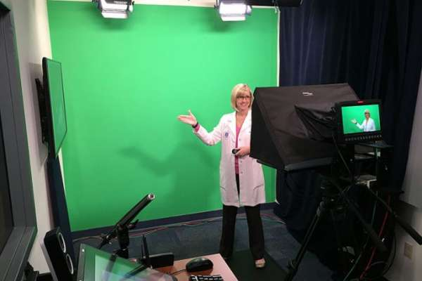 Green Screen with woman in lab coat presenting